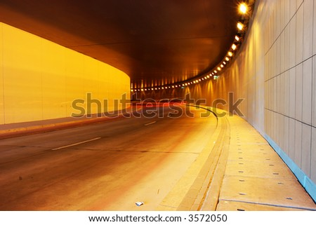 Light trails of vehicles moving in the tunnel - long exposure - stock photo