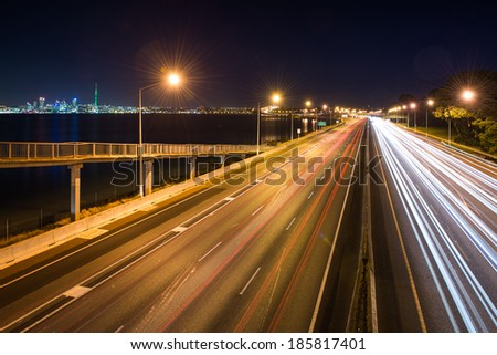 Light trails on a motorway with Auckland City in the background - stock photo