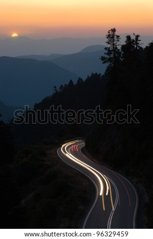 light trails on a winding road of mountain at sunset - stock photo