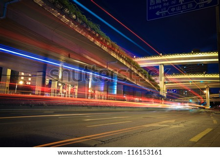 light trails on city road with highway viaduct - stock photo
