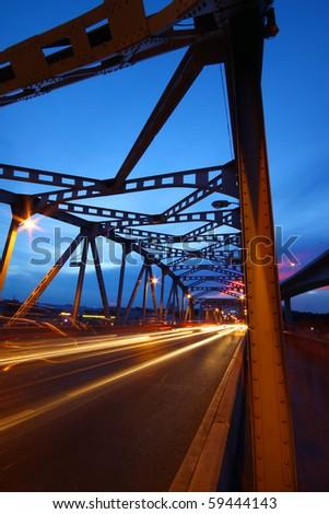 light trails on the bridge road at twilight - stock photo