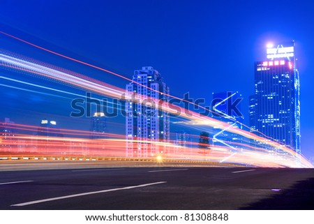 light trails on the highway with modern building background at night - stock photo