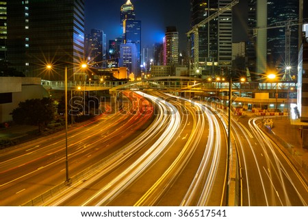 Light trails on the modern building background in Hong Kong, China - stock photo