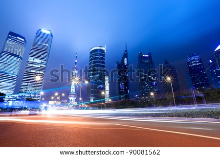 light trails on the street with modern building background in shanghai,China. - stock photo