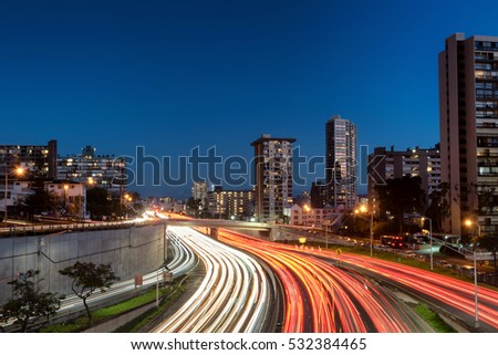Light trails over H1 highway in downtown Honolulu, Hawaii at sunset golden hour