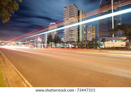 light trails over modern city at night  (broadbeach,gold coast,qld,australia) - stock photo