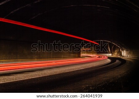 Light tralight trails in tunnel. Art image. Long exposure photo taken in a tunnel ils in tunnel.  - stock photo