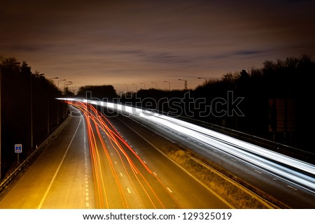 Light trials on a motorway at night - stock photo