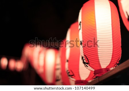 Light up traditional red and white Japanese rice paper balloons with unidentified characters at a festival in Tokyo, Japan - stock photo