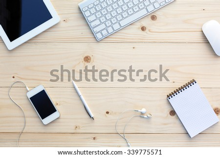 Light wooden Background and modern Business Items on Desk Office Computer Keyboard and Mouse White Pen Tablet PC opened Notepad Earphones dynamic Diagonal alignment  - stock photo