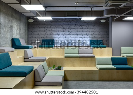 Light wooden benches with multi-colored seats. Seats are made up of pillows. At the back on bench there is a digital clock which made from the transparent rectangles. Left wall is from concrete and