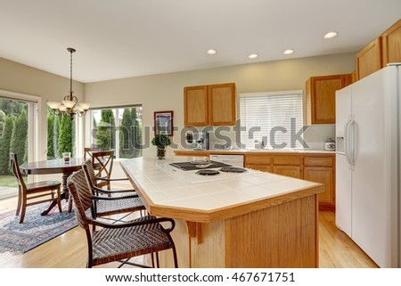 Light wooden kitchen interior with kitchen island and wicker stools. View of dining table set. Northwest, USA