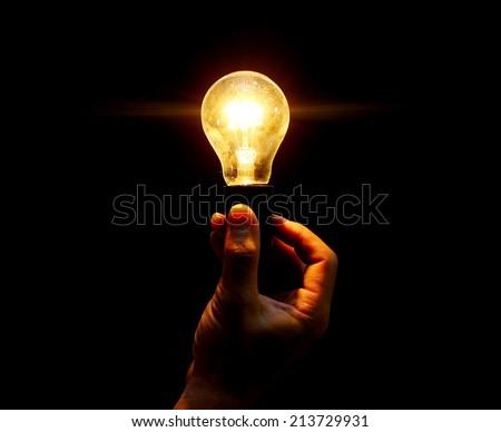 lightbulb held in hand on black background - stock photo