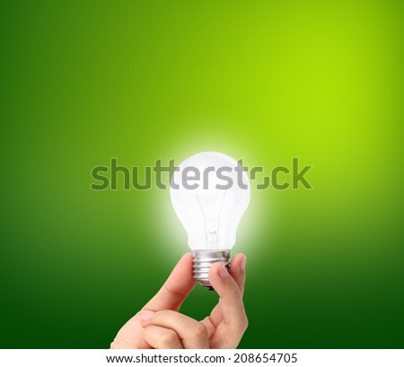 lightbulb hold in hand on green background - stock photo