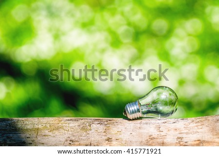 Lightbulb in bright light in a green forest - stock photo