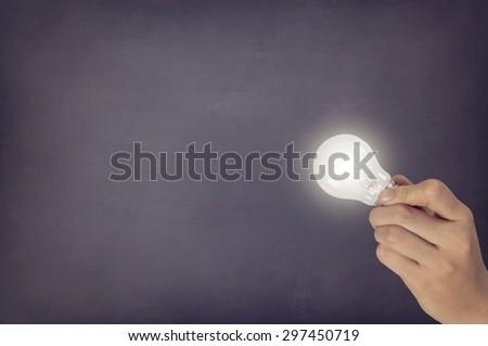 Lightbulb in hand on blackboard - stock photo