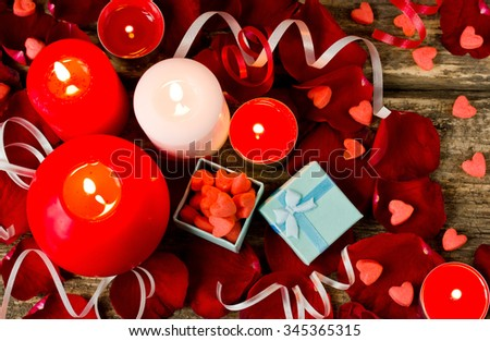 Lighted candles in the petals of red roses and sweet candy heart, romantic background - stock photo