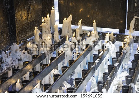 Lighted candles on religious shrine, symbol and belief - stock photo