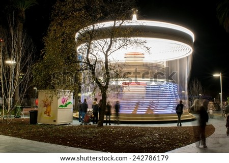 Lighted carousel at night in the city in a long-exposure photo - stock photo