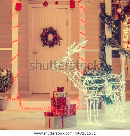 Lighted Christmas deer with gift boxes near the door with wreath decoration. Vintage Christmas concept - stock photo