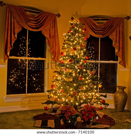 Lighted christmas tree in cozy home - stock photo