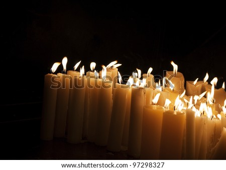 Lighted church candles in dark - stock photo
