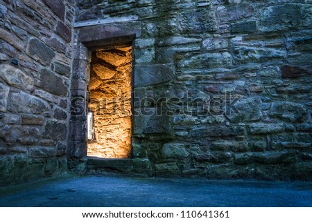 Lighted dorway to the ancient castle - stock photo