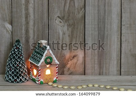 Lighted gingerbread house and evergreen tree by wooden fence - stock photo