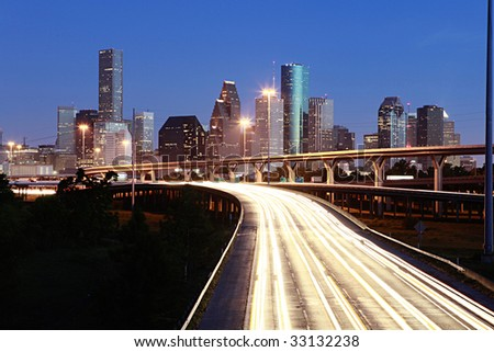 Lighted Houston skyline against blue sky - stock photo