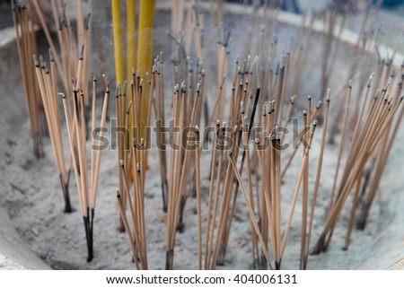 Lighted incense sticks smolder and smoke from the ashes of a Buddhist altar in a temple. - stock photo