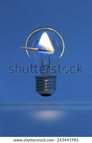 lighted match on a background of the bulb in the dark - stock photo