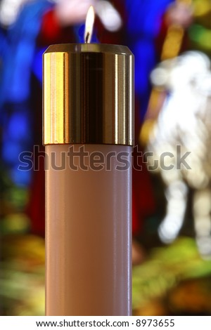Lighted Religious Candle with Blurred Stained Glass Window Background - stock photo