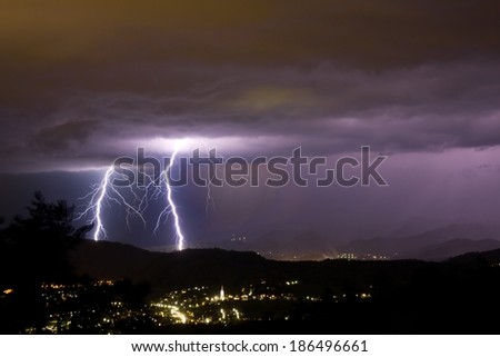lightening bolts behind a city - stock photo