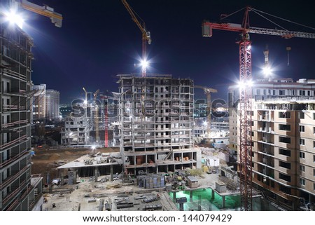 Lightening multi-storey buildings under construction and cranes at night. - stock photo