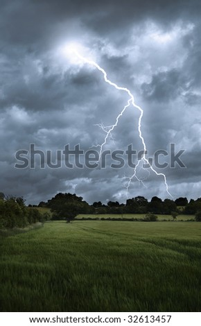 Lightening strikes from a stormy sky over a countryside landscape - stock photo