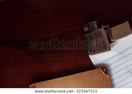 Lighter on table with paper and notes