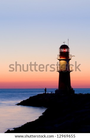 lighthouse after sunset, with fishing man in backlight