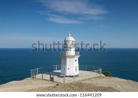 Lighthouse against a blue sky and sea - stock photo