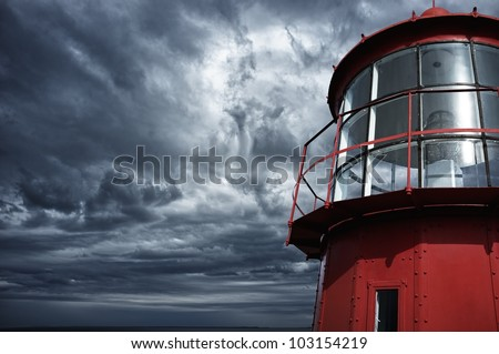 Lighthouse against  stormy sky. - stock photo