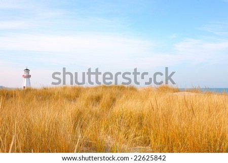Lighthouse and dunes on Lake Michigan - stock photo