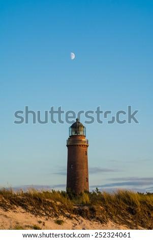 lighthouse and moon at Darss Peninsula - stock photo