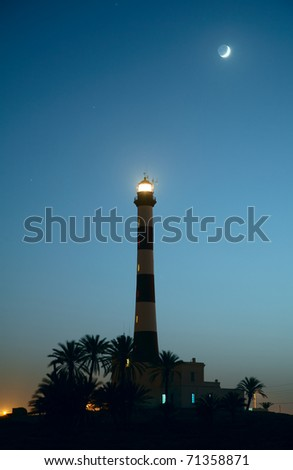 Lighthouse and palm trees in the twilight - stock photo
