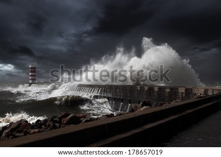 Lighthouse and pier under heavy storm. Enhanced sky. - stock photo