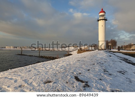 Lighthouse and snow covered jetty - stock photo