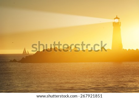 Lighthouse and surf boat with light beam at sunset - stock photo