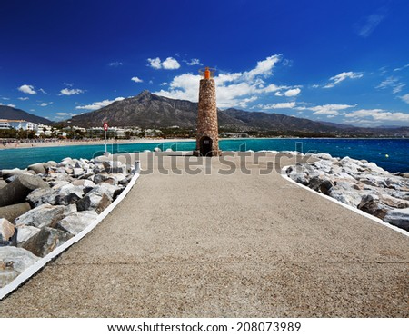Lighthouse at the end of breakwater in the Puerto Banus in Marbella, Spain. Marbella is a popular holiday destination located on the Costa del Sol in the southern Andalusia - stock photo