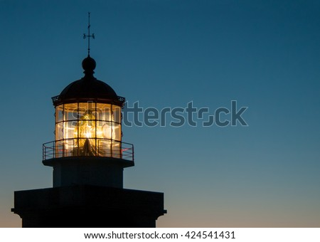 lighthouse beaming against clear night sky