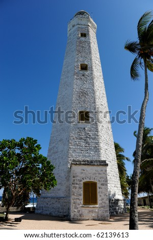 lighthouse between palms - stock photo