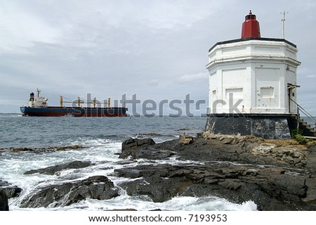 Lighthouse, Bluff, New Zealand with container ship being piloted out of the harbor - stock photo