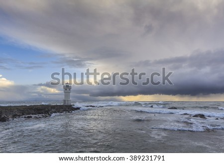 Lighthouse, breaking waves and afternon sun behind a dark cloud - stock photo